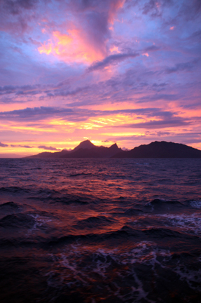 A gorgeous sunset over the volcanic island of Moorea in the Society Islands of French Polynesia