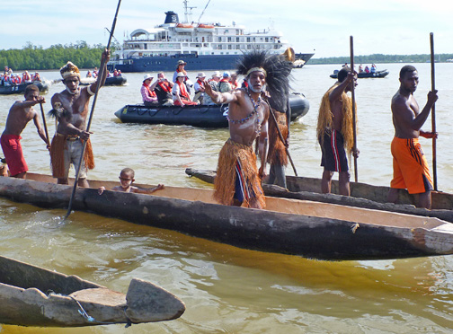 Asmat Warriors paddling out to the ship and the waiting Zodiacs