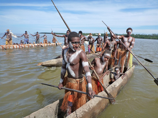 Asmat men and boys greeting us and then grabbing onto our Zodiacs for a tow.