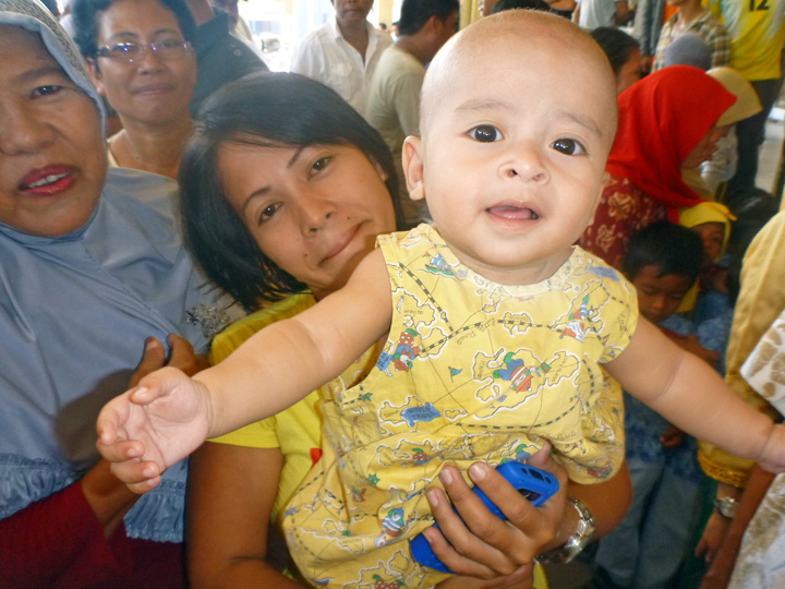 Someone proudly holding up their beautiful baby for a photo with a visitor outside a welcome ceremony in Toli Toli, Sulawesi, Indonesia.