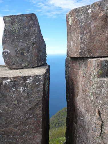 Rock columns at the summit of Bishop & Clerk with the Tasman Sea beyond.