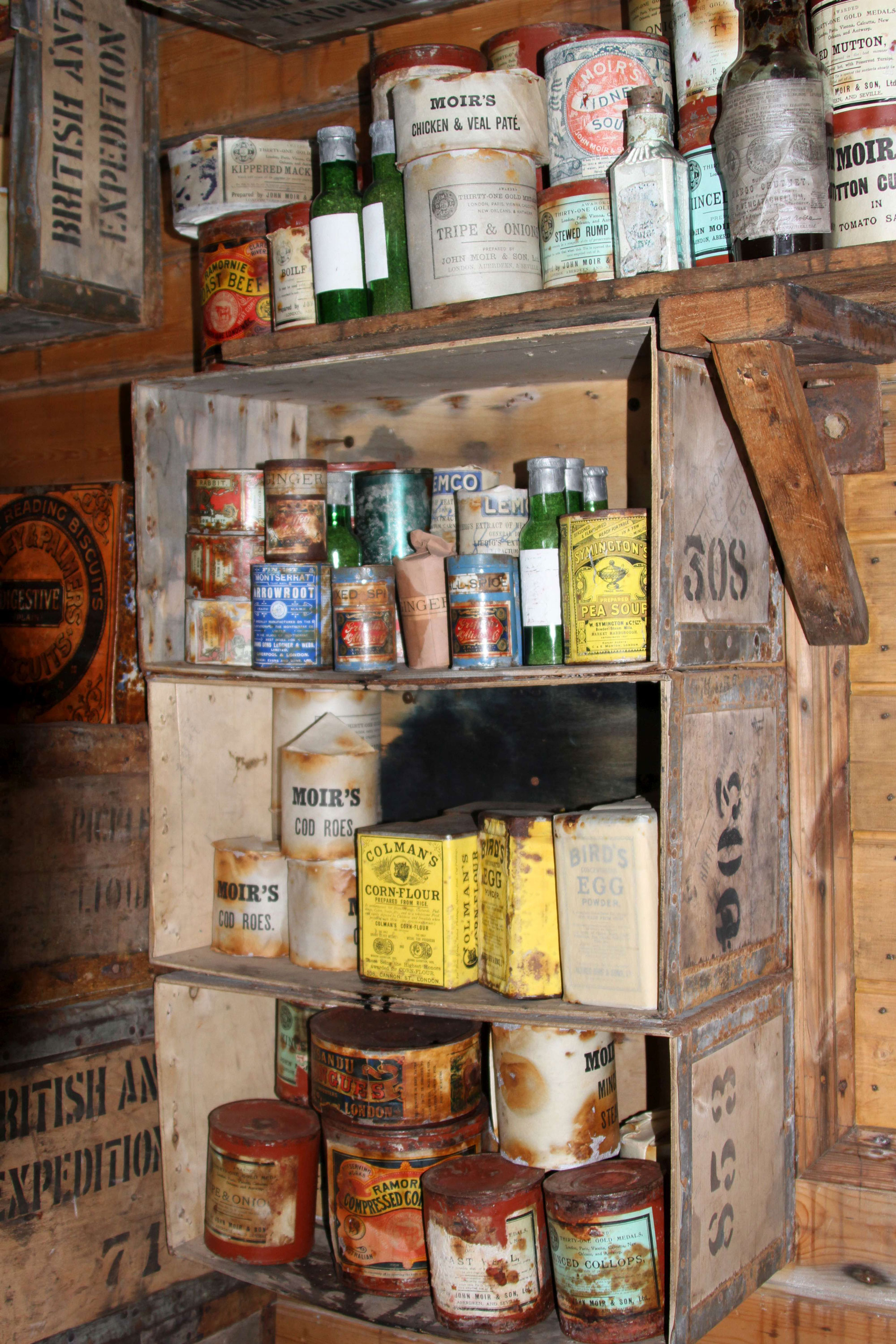An assortment of provisions inside Shackleton's hut.  The shelves are made from packing crates for his 1907 expedition.