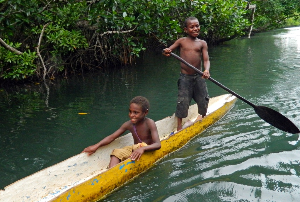 A typical sight in PNG -- kids in their canoes trying to catch a ride on our Zodiacs, or surfing in our wakes.