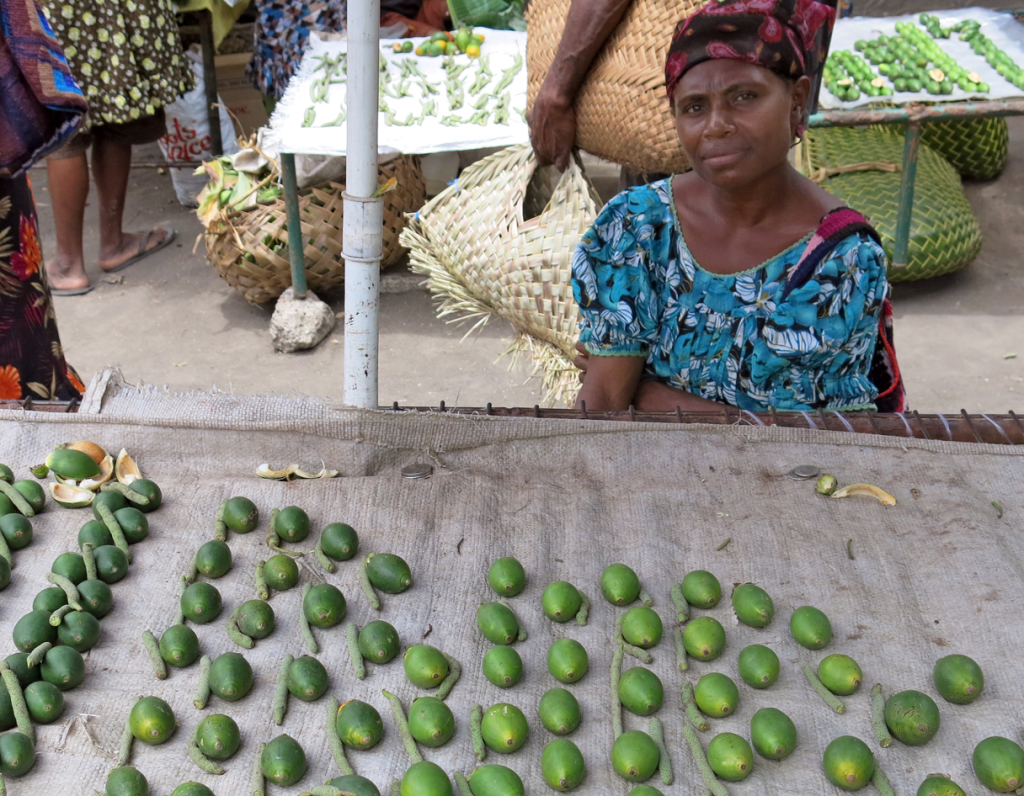 A lady sits at her market stall selling betel nut and the pepper pods that accompany.