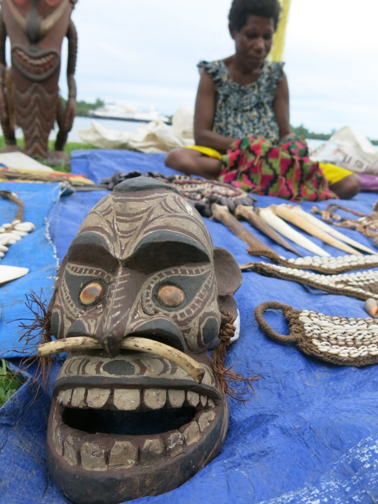 Carvings and necklaces on display and for sale.  The woman is making a traditional bag called a 'bilum'