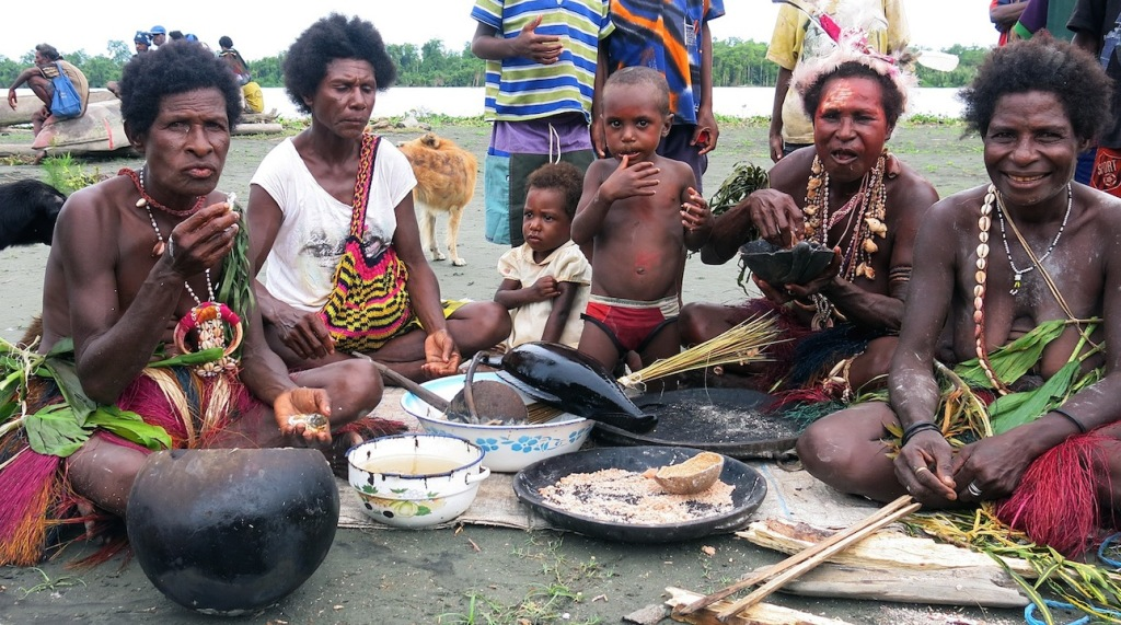 This family gathered to prepare lunch around a small pile of mangrove branches burning on the ground near the Sepik River.