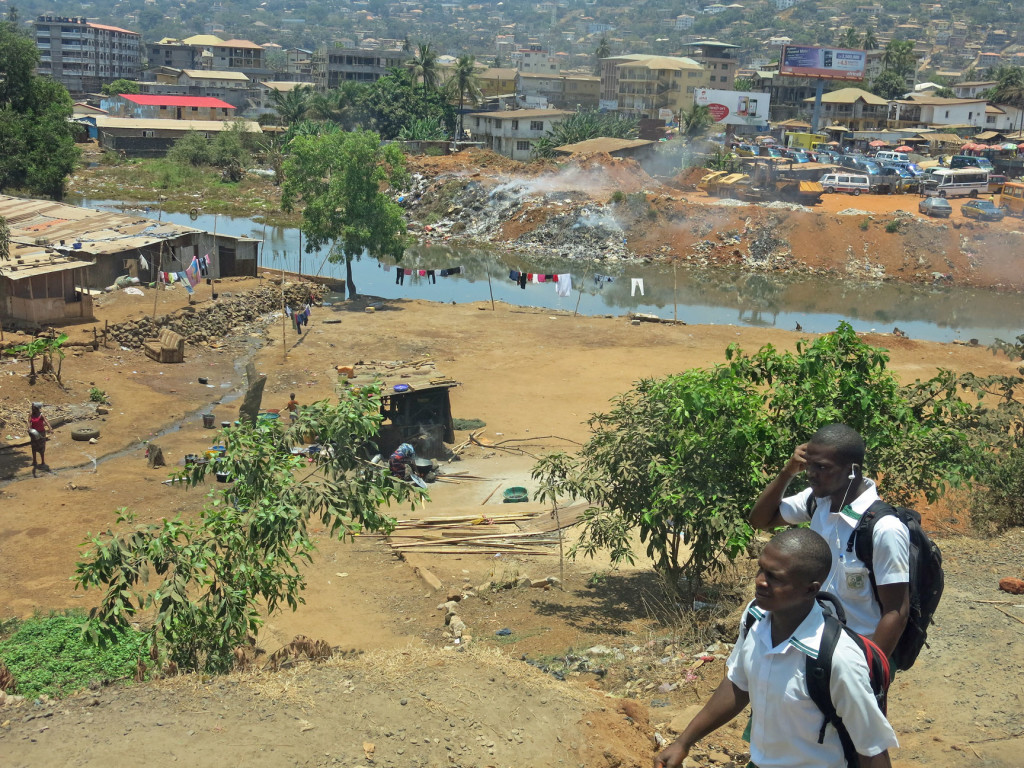 Students walking home on the Sierra Leone roadside as piles of trash smolder on the riverbank behind them.